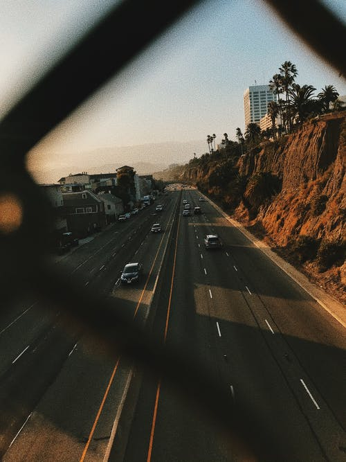 From above of contemporary cars driving on smooth surface of roadway near hills and houses