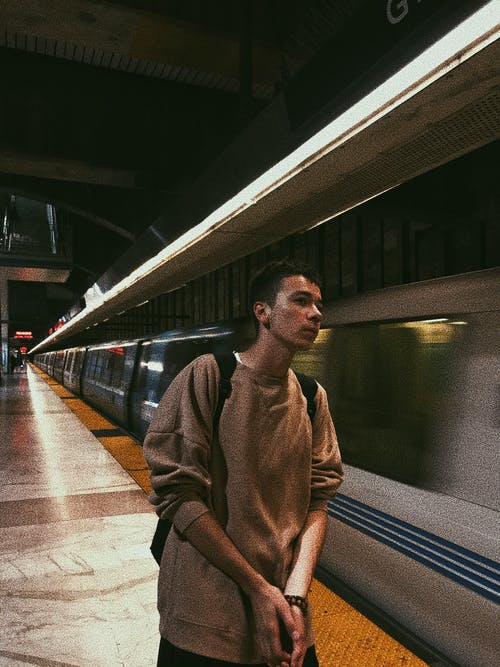 Young man waiting for train on platform