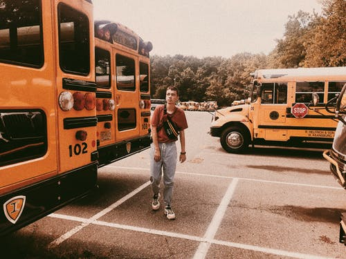 Stylish young man walking on parking lot with school buses