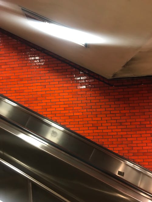 Shiny metallic handrail of escalator with bright brick wall under light of lamp in underground