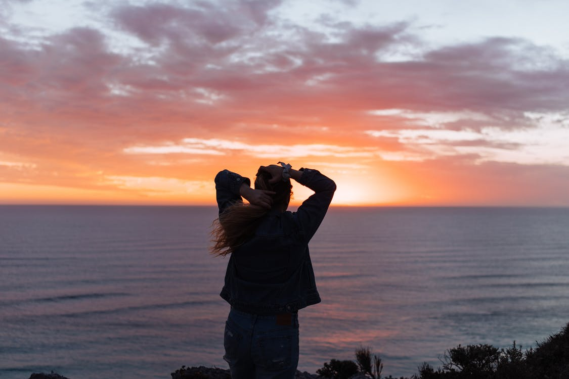 Anonymous female standing near sea