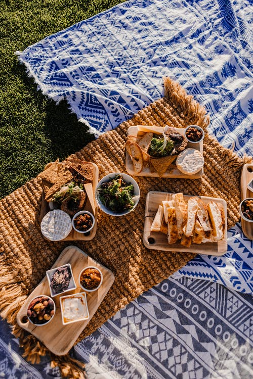 Bread and snacks on blanket in meadow