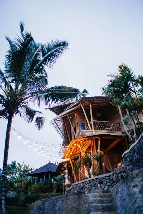 Wooden cottage decorated with glowing garlands on exotic seashore