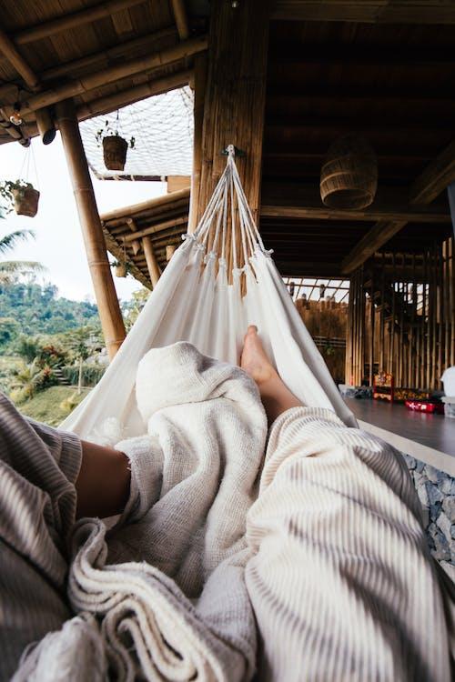 Crop barefoot traveler chilling on white cozy hammock under blanket on terrace of house in daytime