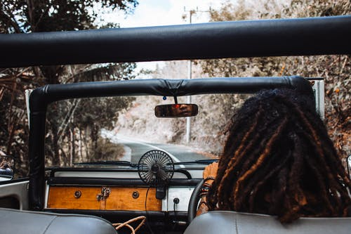Back view of unrecognizable traveler with stylish dreadlocks spinning steering wheel while driving car and reflecting in small mirror