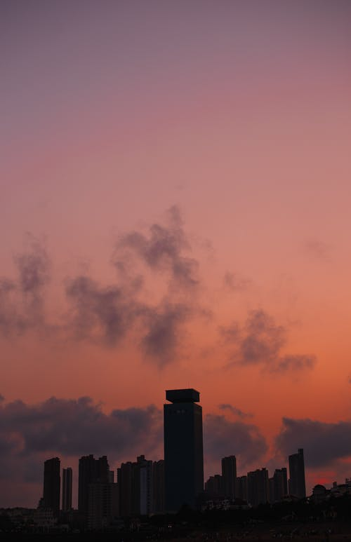 Vivid pink sky over tall constructions in city in evening