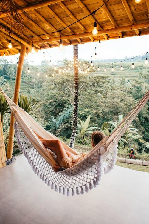 Slender woman resting in hammock under glowing garlands