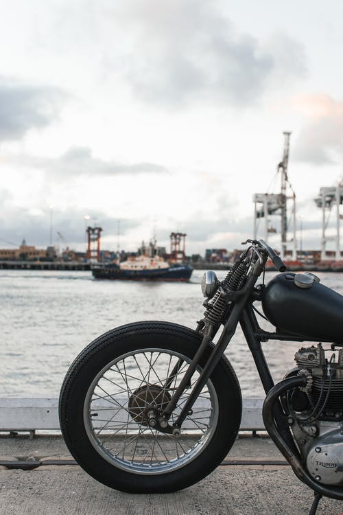 Classical bike parked next to port under gray cloudy sky