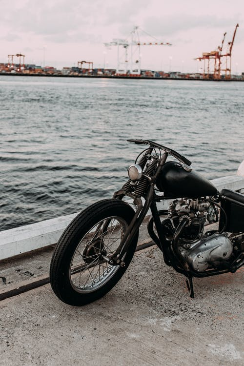 Vintage motorcycle parked on embankment of river