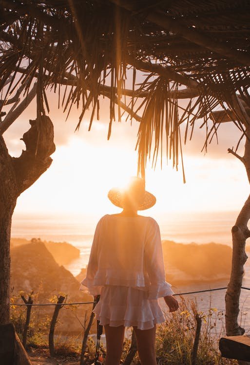 Back view of anonymous female observing sunset in hills while standing near wooden terrace in back lit