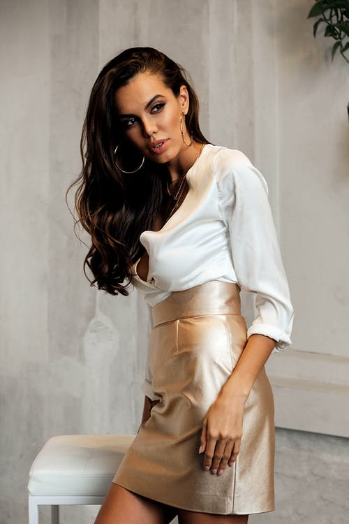 Elegant woman in stylish clothes standing near chair