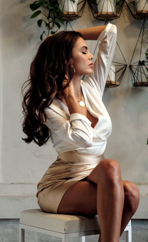 Alluring woman in elegant outfit sitting on chair
