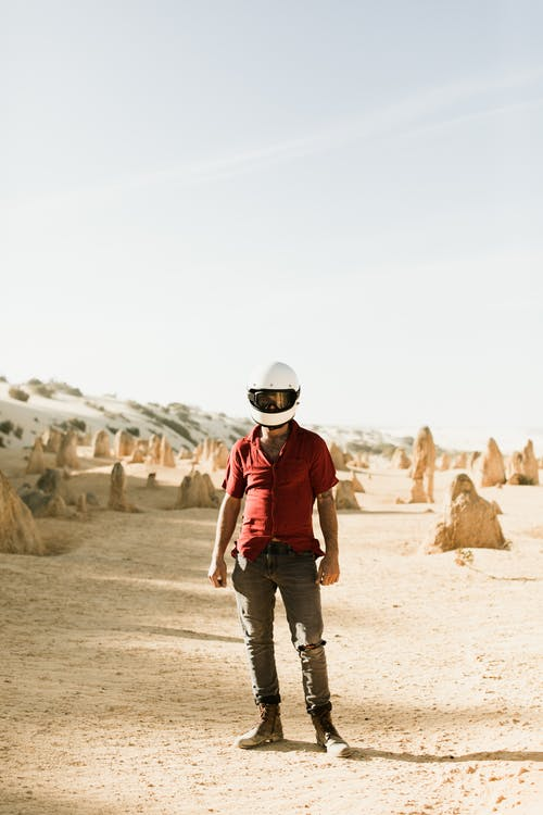 Full body of biker in casual outfit and helmet standing in dry sandy desert with rough stones under cloudy sky