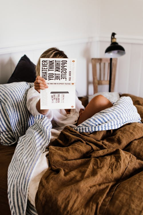 Anonymous woman with novel in bed