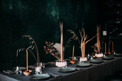 Creative design of festive table with dry plants in vases and tableware in cozy restaurant