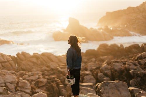 Young woman on rocky coast near sea