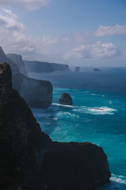Breathtaking view of rough rocky cliffs in rippling ocean water under blue sky with clouds