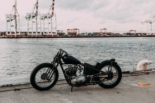 Vintage motorcycle on asphalt embankment near rippling river water against industrial area in city