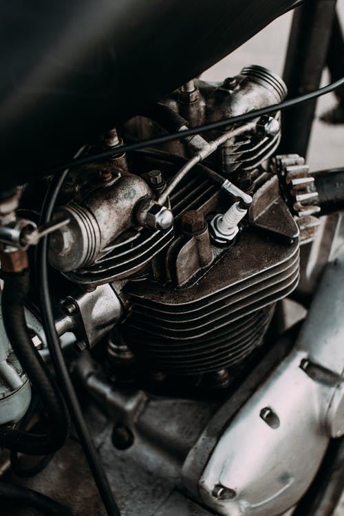Part of motorbike with engine and metal details on asphalt road of city