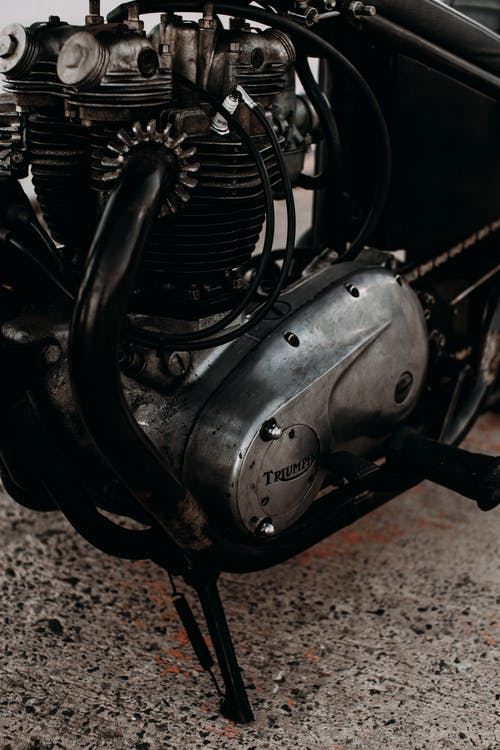 Engine under metal gear with wires of aged motorcycle parked on rough pavement in daytime