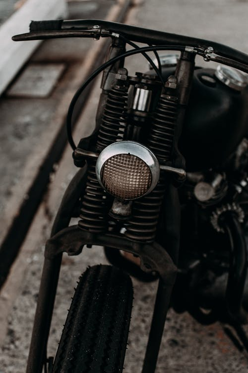 Headlight of motorcycle parked on pavement in daylight