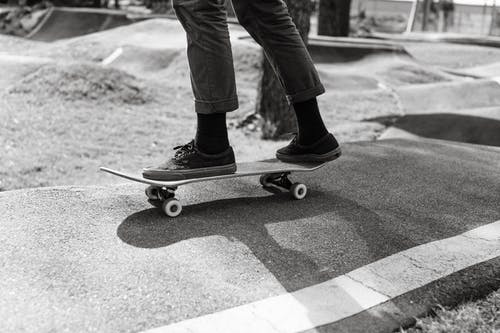 Crop athlete skateboarding on wavy road in town