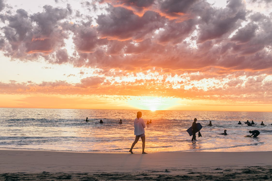 Breathtaking sunset on sandy beach and people enjoying time while swimming and surfing on tropical resort