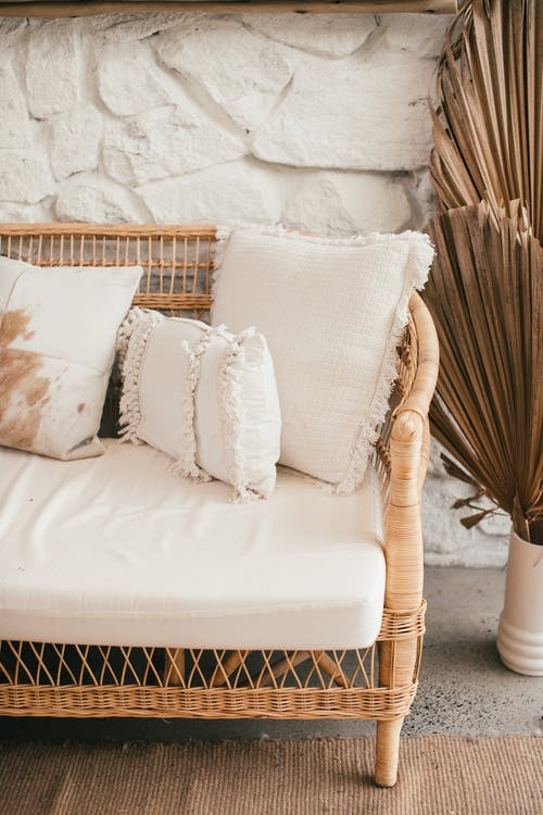 Wicker sofa with decorative cushions near stone wall