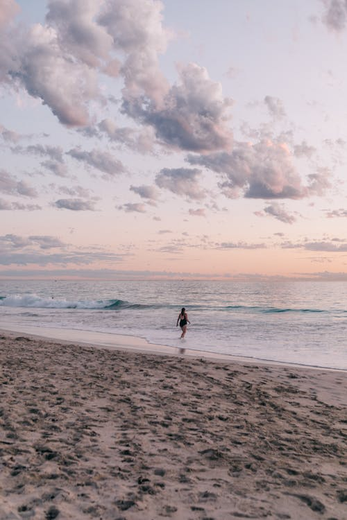 Unrecognizable traveler on wet sea beach at sunset