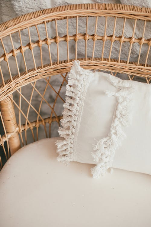 Wicker couch with decorative cushion in daylight