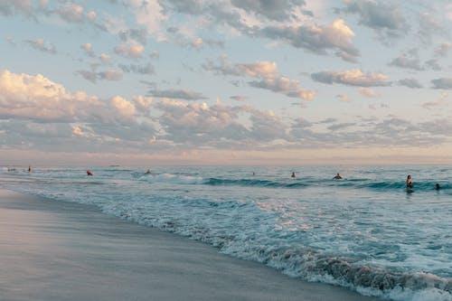 Anonymous travelers swimming in wavy ocean at sundown