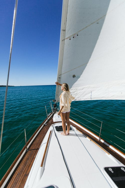 Unrecognizable traveler contemplating sea from yacht during summer trip