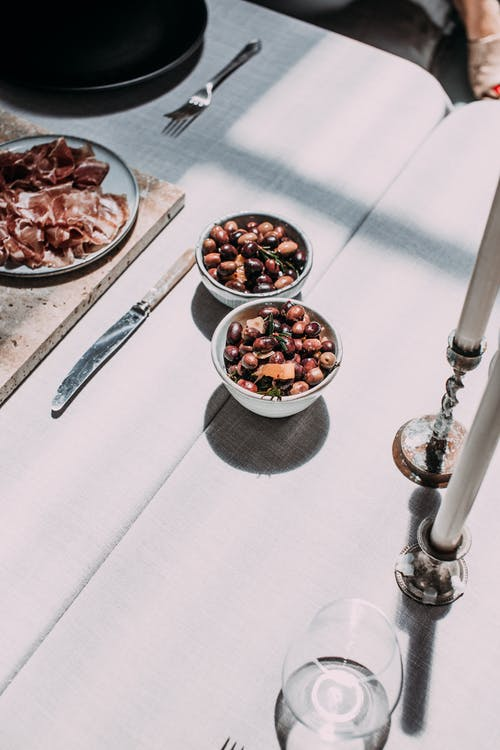 Assorted beans in bowls near smoked ham on table