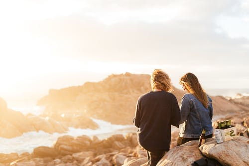Unrecognizable couple standing on rocky shore