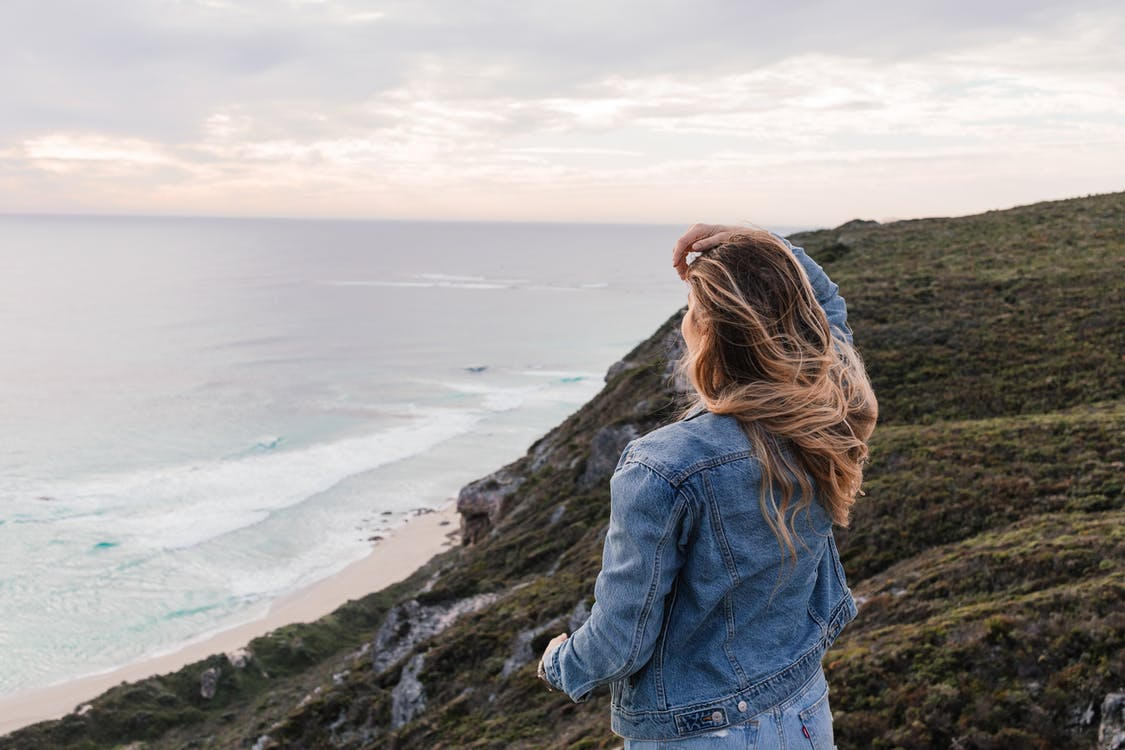 Back view of unrecognizable female with flying hair standing near sea on edge of rocky coast with hand on head and looking into distance