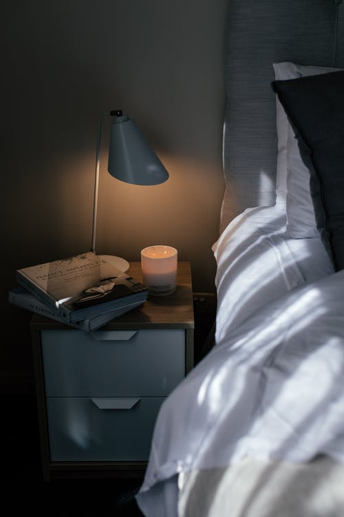 Cozy bed with crumpled sheet and pillows near nightstand with textbooks and lamp in bedroom
