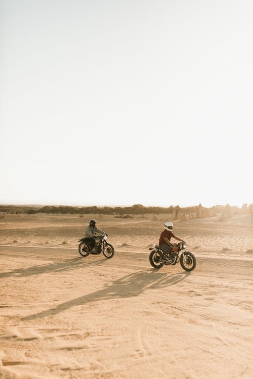 Unrecognizable bikers riding motorcycles in desert in sunlight