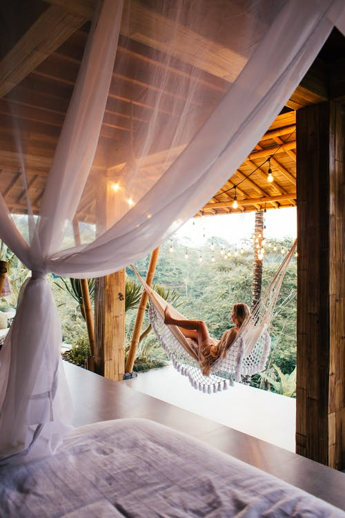 Side view of unrecognizable barefoot female traveler lying in hammock on bamboo terrace against bed under canopy