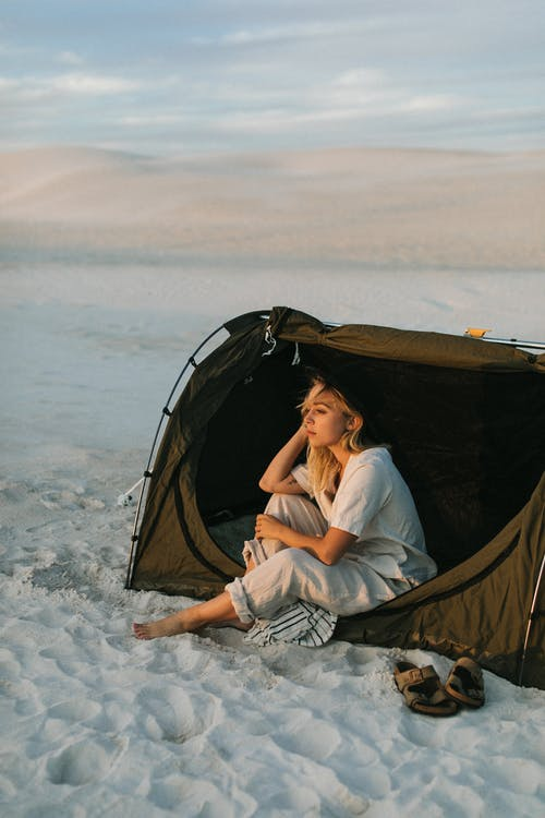 Dreamy tourist in tent contemplating desert during summer trip