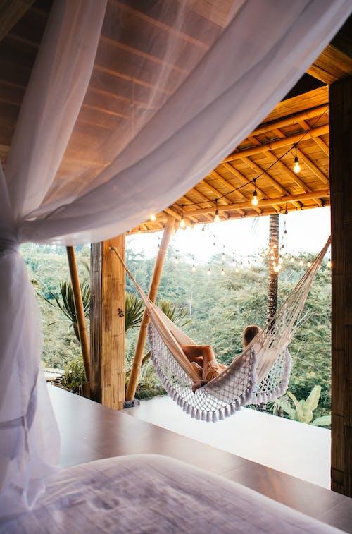 Unrecognizable traveler in hammock against bed in tropical resort