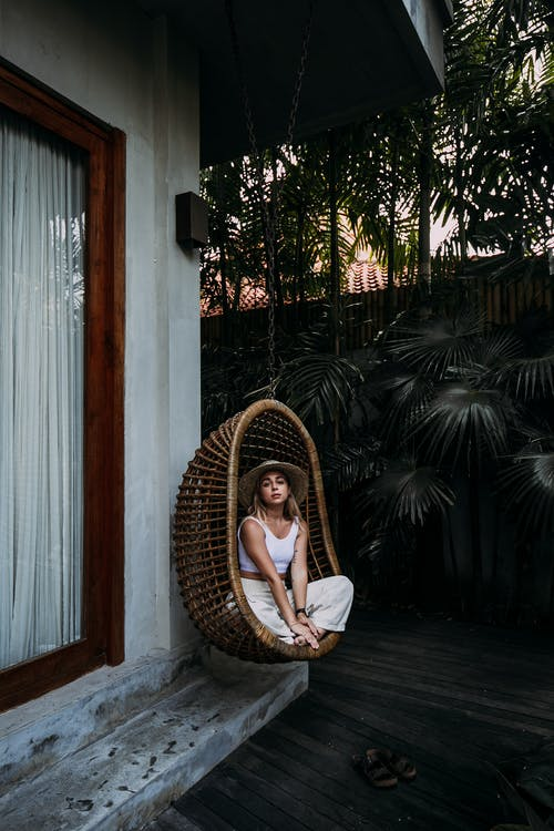 Feminine woman resting in hanging chair near house
