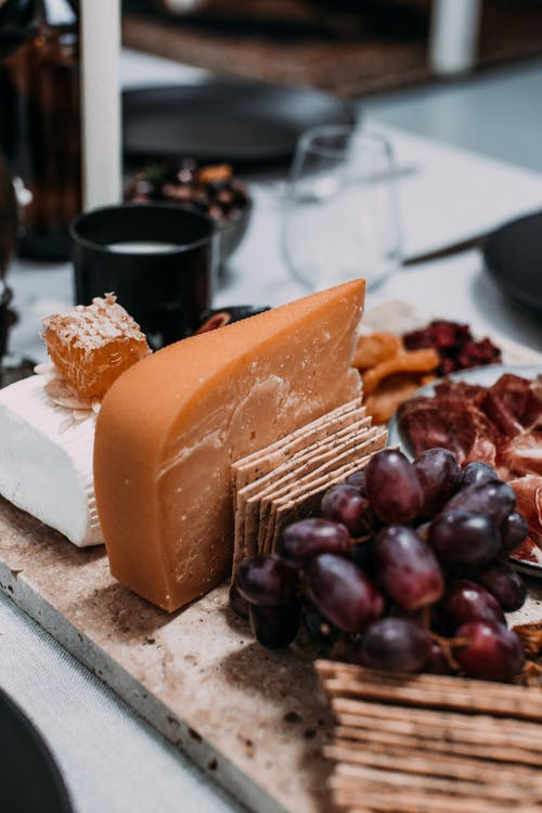 Delicious cheese with grapes and crackers on table