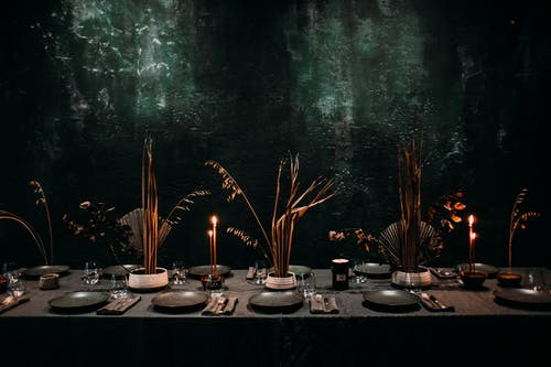 Ceramic plates with fork and knife placed on napkin on banquet table with candles and dried plants