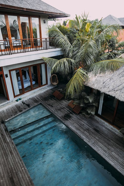 From above of wooden cottage with balcony located among tropical exotic trees with blue pool