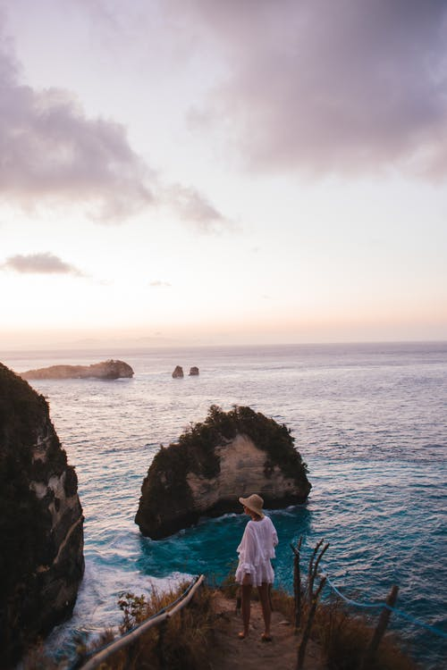 High angle back view of faceless female traveler wearing straw hat standing near rippling sea at sundown