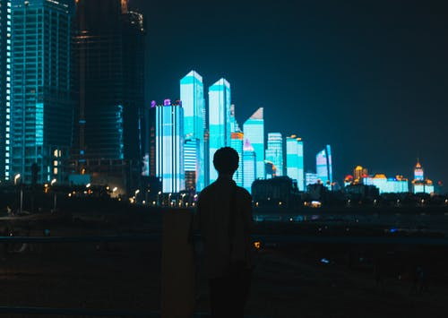 Back view of anonymous male enjoying view of high modern illuminated towers of metropolis at night