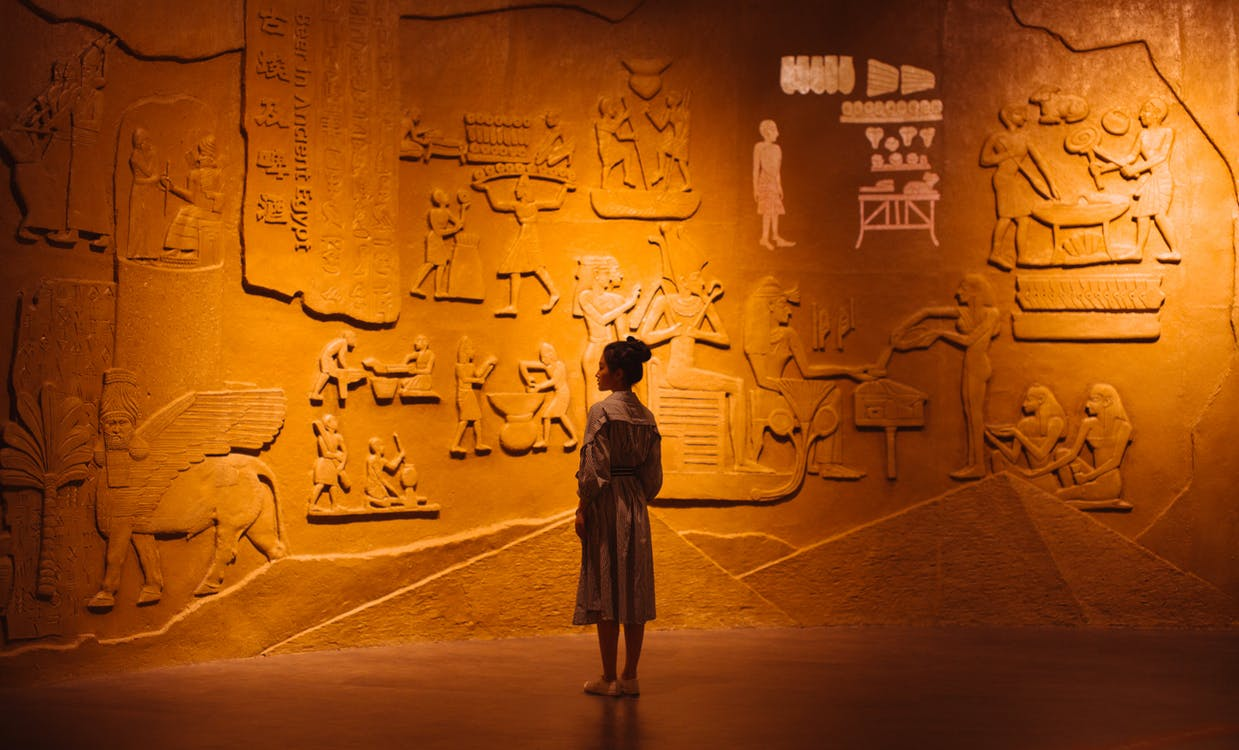 Back view of anonymous female traveler standing near ancient wall with Egyptian engraving