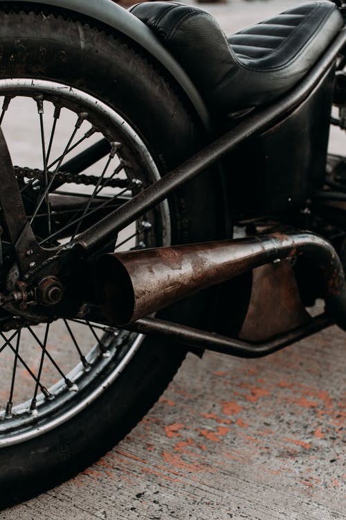 Motorbike with leather saddle and exhaust pipe