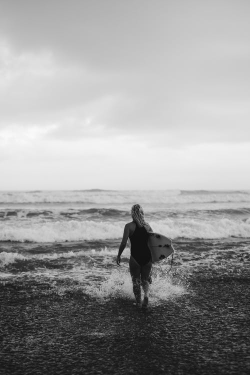 Woman with surfboard running in waving sea