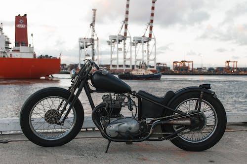Retro motorbike in river port against ships